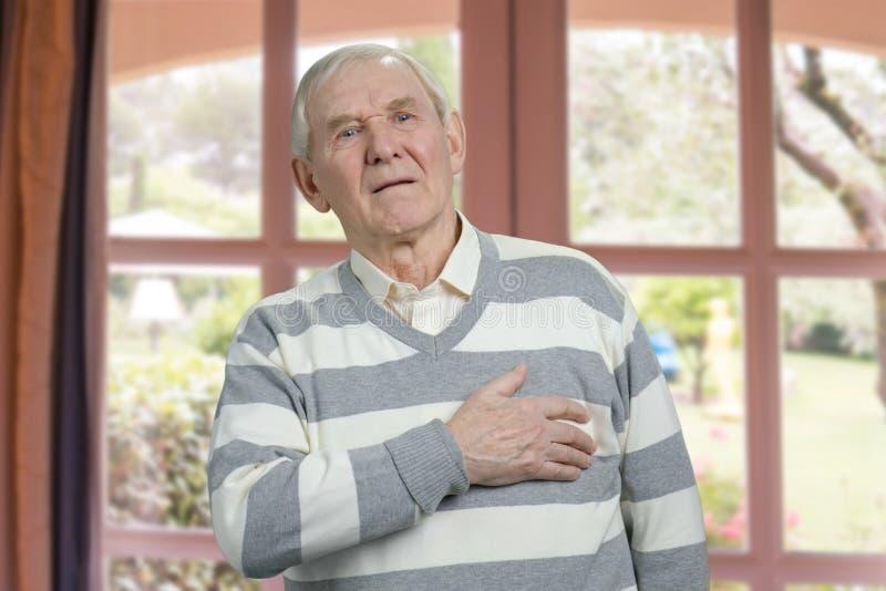 Oude mens die borstpijn hebben stock afbeelding