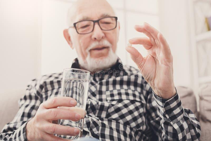 Oude mens die een glas water en pillen hebben ter beschikking stock foto's