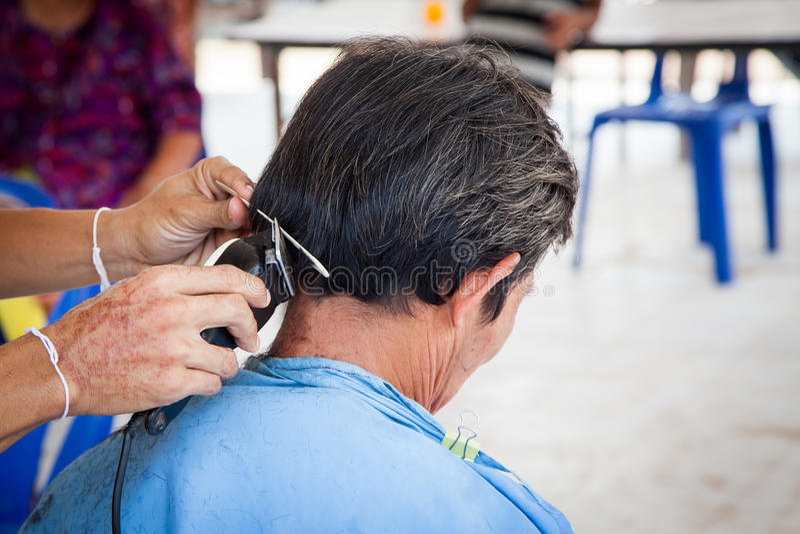 Oude mens die een kapsel met een haarclippers hebben royalty-vrije stock afbeeldingen