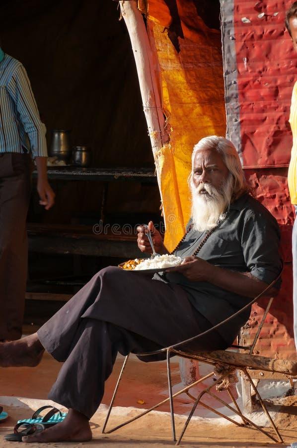Oude mens die een maaltijd in straatmarkt eten in Khajuraho stock foto's