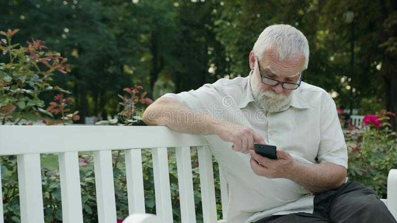 Oude Mens die een Telefoon in openlucht met behulp van stock foto