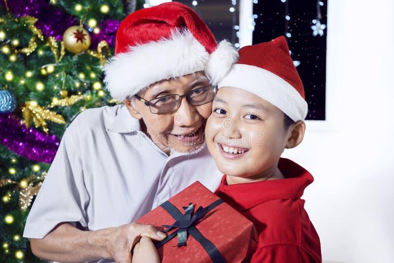 Oude mens die giftdoos voor zijn kleinzoon geven royalty-vrije stock fotografie