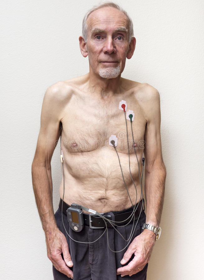 Oude mens die hartmonitor dragen stock afbeeldingen