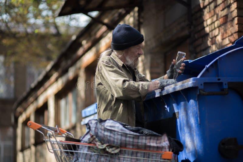 Oude mens die lege flessen verzamelen om geld te verdienen stock foto