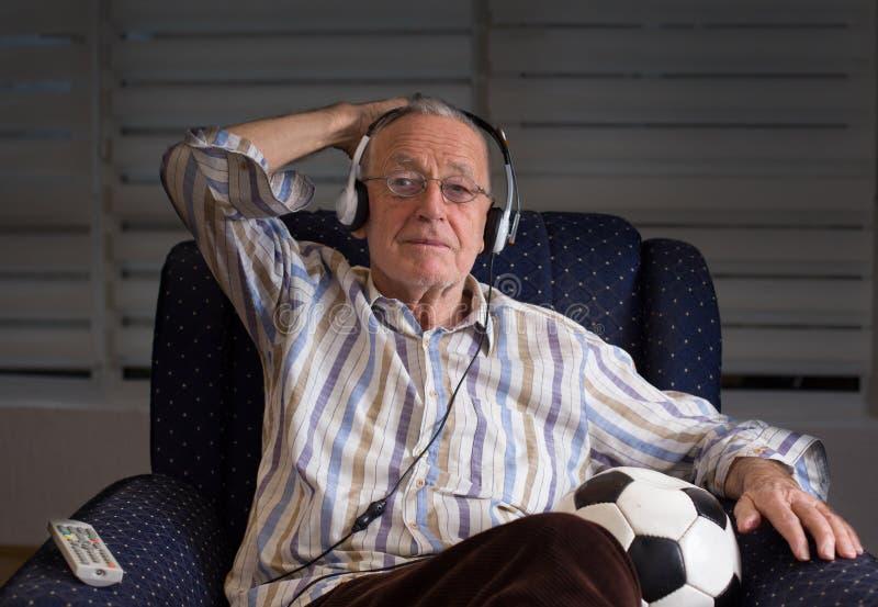 Oude mens die met voetbalbal op TV letten royalty-vrije stock afbeeldingen