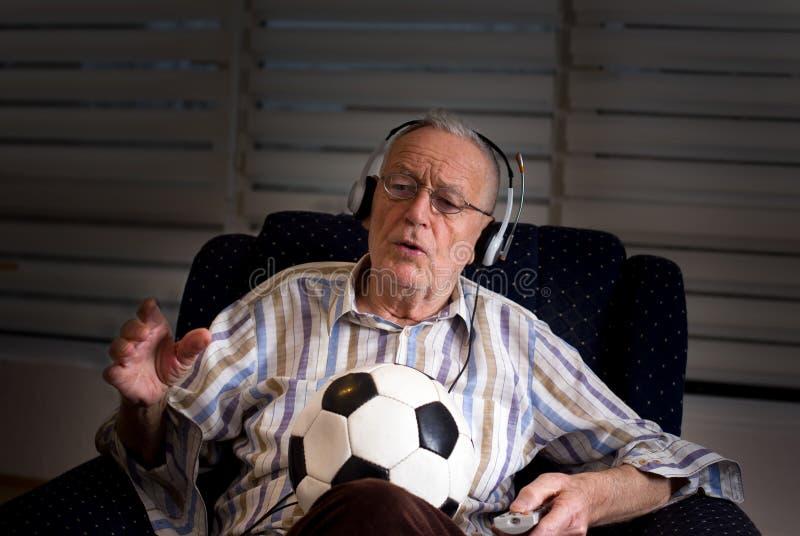 Oude mens die met voetbalbal op TV letten royalty-vrije stock afbeelding