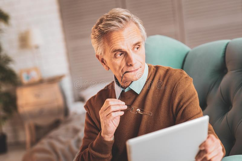 Oude mens die nadenkend na het lezen van nieuwsgierig nieuws voelen royalty-vrije stock foto