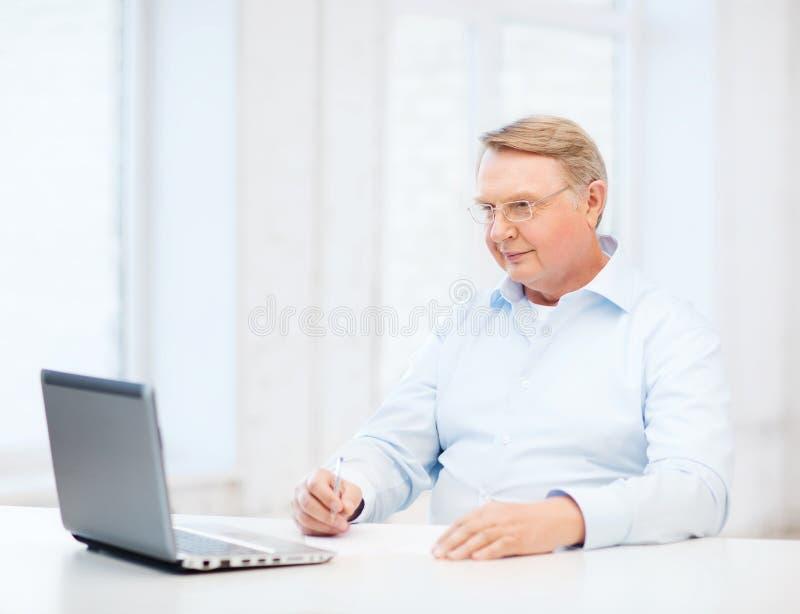 Oude mens die in oogglazen een vorm thuis vullen stock afbeelding