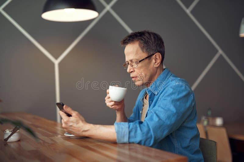 Oude mens die op mobiele telefoon in koffie kijken stock foto