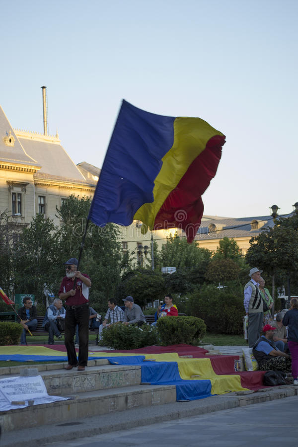 Oude mens die Roemeense vlag golven stock foto