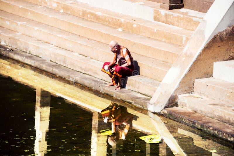 Oude mens die typische robe dragen die bij de Tempelpool van Sree Padmanabhaswamy tijdens de zonnige dag in Trivandrum, India sit stock foto's