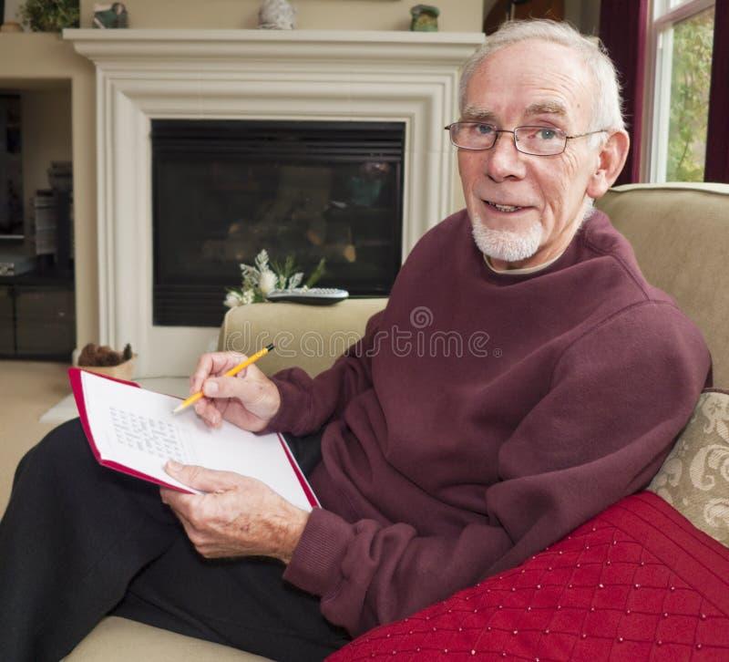 Oude mens die woordraadsel doet royalty-vrije stock afbeelding