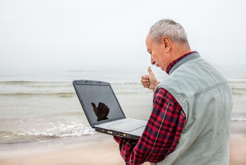 Oude mens die zich op het strand met laptop bevinden stock afbeeldingen