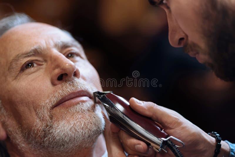 Oude mens die zijn die baard krijgen door kapper wordt geschoren stock foto
