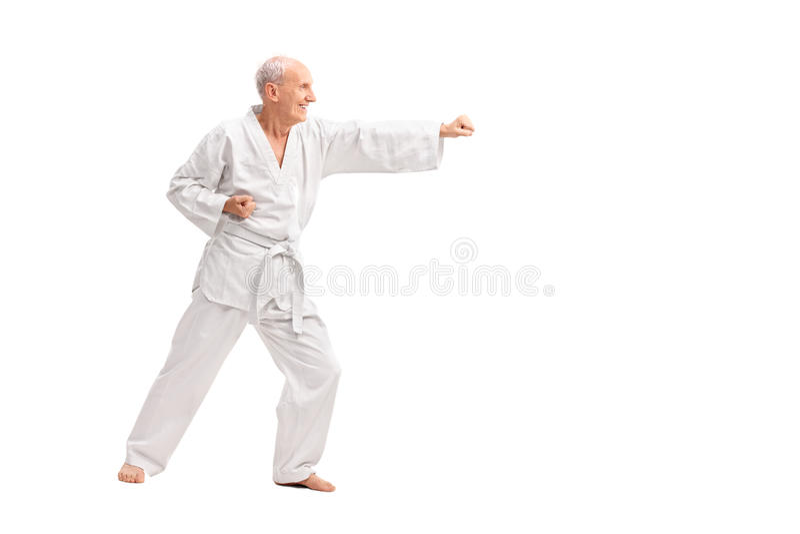 Oude mens in een witte kimono het praktizeren karate stock foto