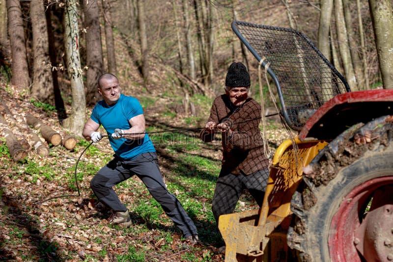 Oude mens en een sterke mens die met een tractor werken stock afbeeldingen