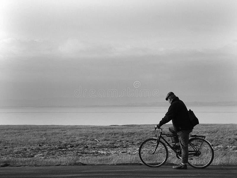 Oude mens en fiets stock afbeelding