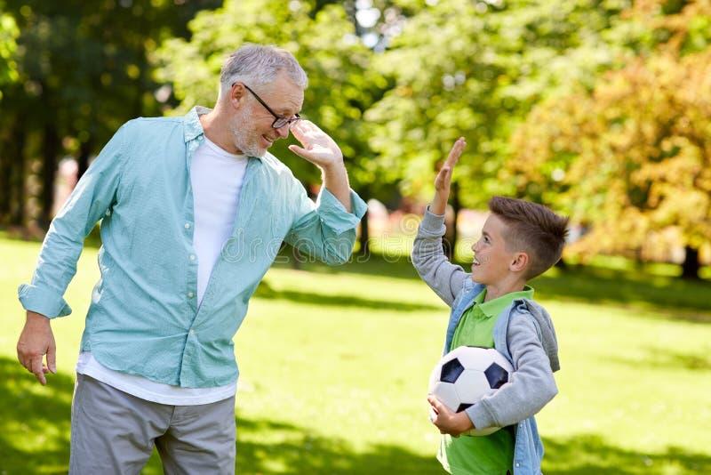 Oude mens en jongen die met voetbalbal hoge vijf maken stock fotografie