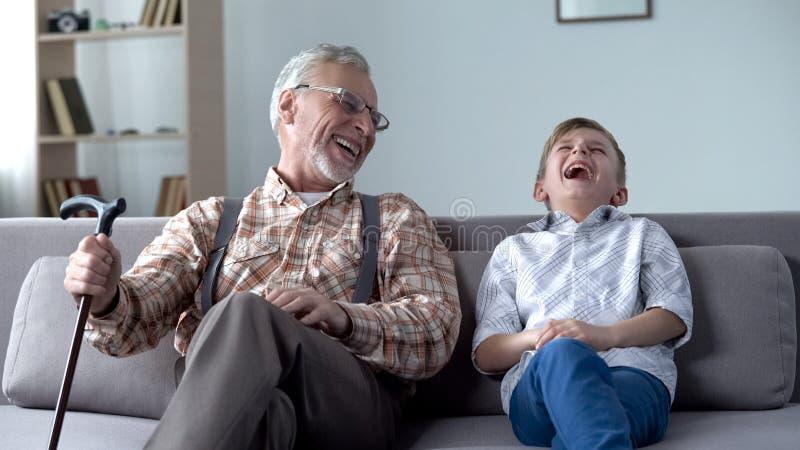 Oude mens en jongen die, samen gekscherend, waardevolle pretogenblikken echt lachen stock afbeeldingen