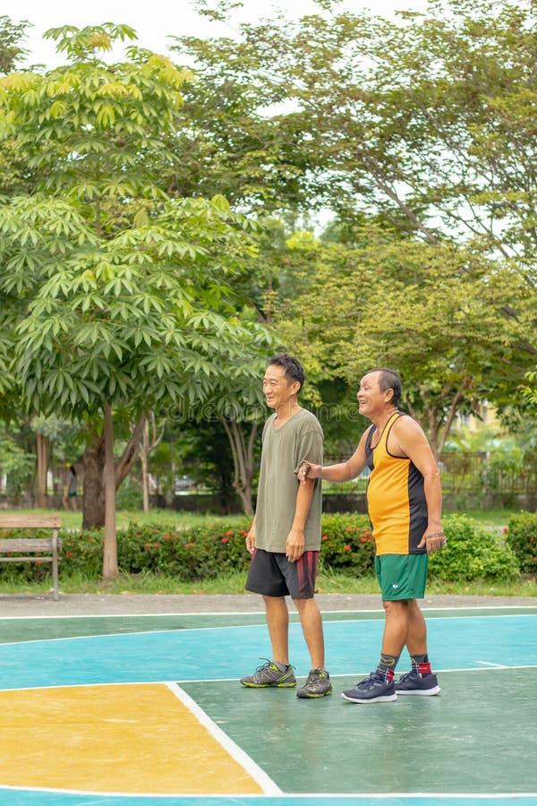 Oude mens gelukkig met oefening om basketbal bij BangYai-Park te spelen royalty-vrije stock afbeeldingen