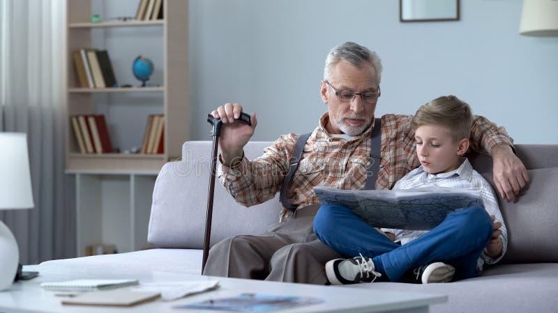Oude mens het bekijken kaart met kleinzoon, die reis samen bespreken, lerend aardrijkskunde stock afbeeldingen