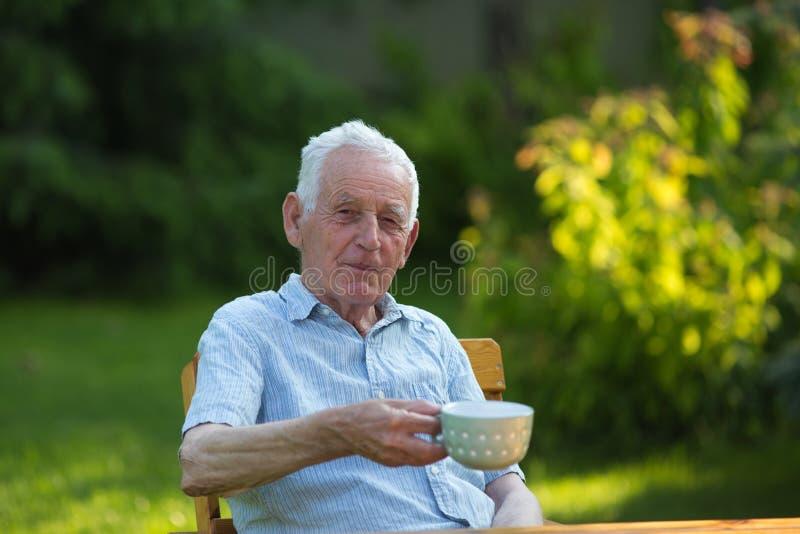 Oude mens het drinken thee in tuin stock afbeelding