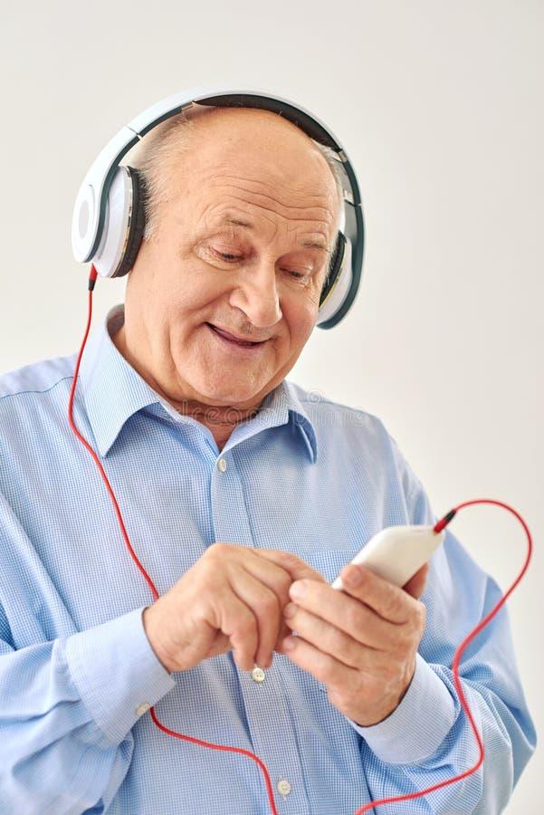 Oude mens het luisteren muziek op hoofdtelefoons stock foto's