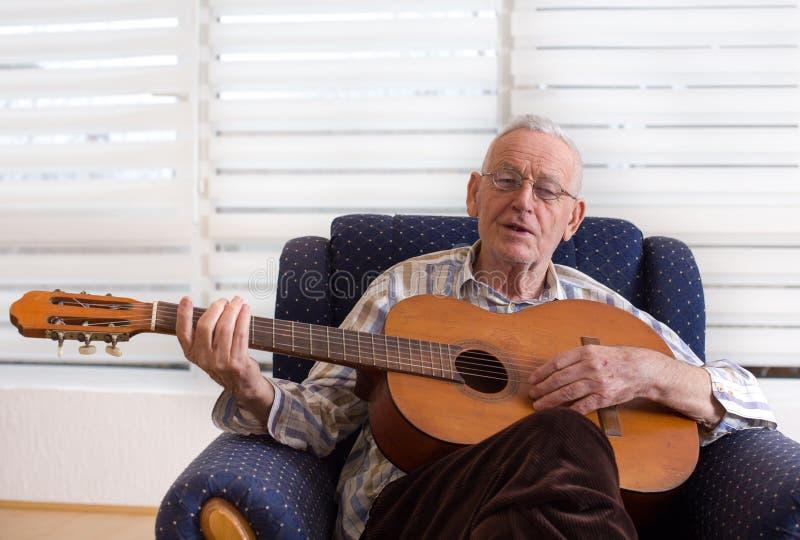 Oude mens het spelen gitaar thuis stock afbeelding