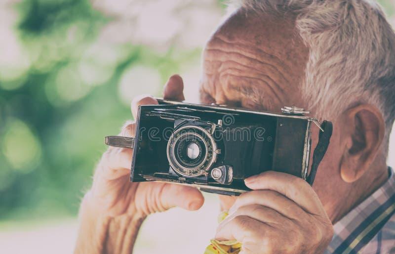 Oude mens met analoge camera stock afbeelding