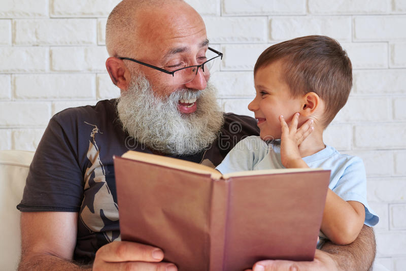 Oude mens met baard met zijn kleinzoon die een boek in leunstoel lezen royalty-vrije stock foto's