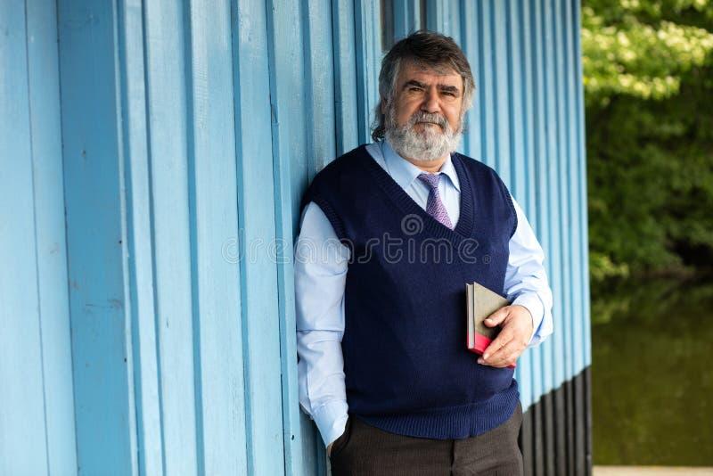 Oude mens met een boek op een portiek stock fotografie