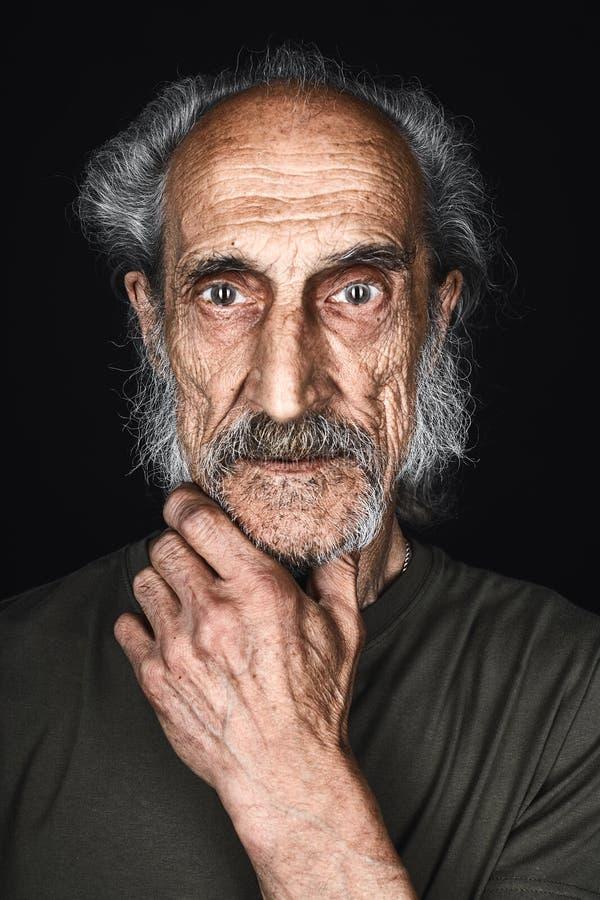 Oude mens met een plam op de kin die bij de camera met doen schrikken uitdrukking loking royalty-vrije stock foto's