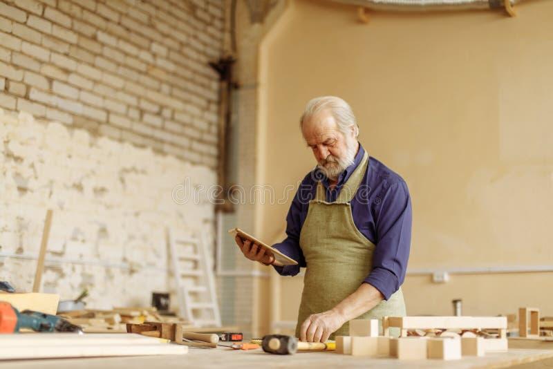 Oude mens met grijze haar, snor en baard die met tablet in de garage werken stock foto's