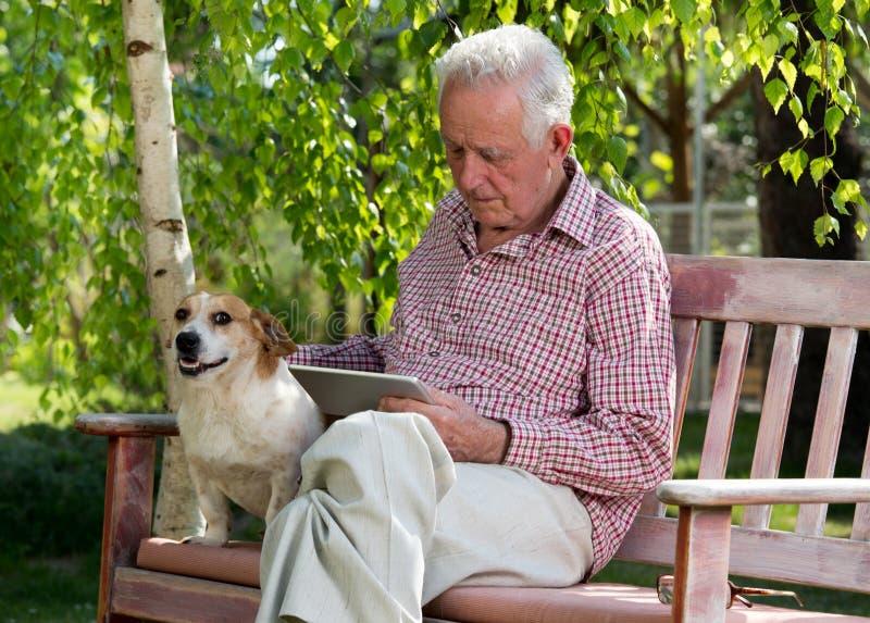 Oude mens met hond en tablet in tuin stock afbeeldingen