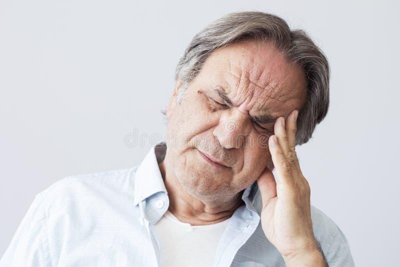 Oude mens met hoofdpijn stock foto