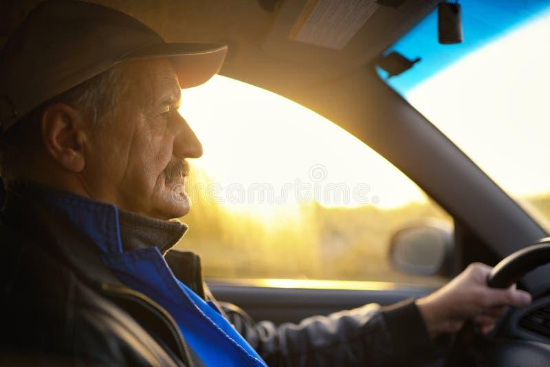 Oude mens met snorren die een auto drijven Zonstralen door een glas stock foto's