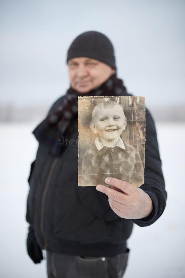 Oude mens met zijn foto als kind stock afbeeldingen