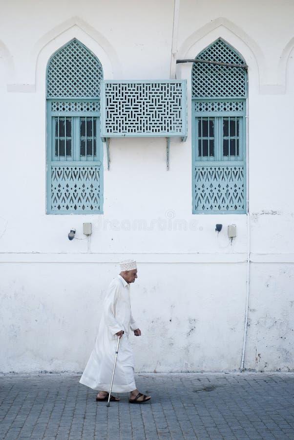 Oude mens in muscateldruif Oman stock foto's