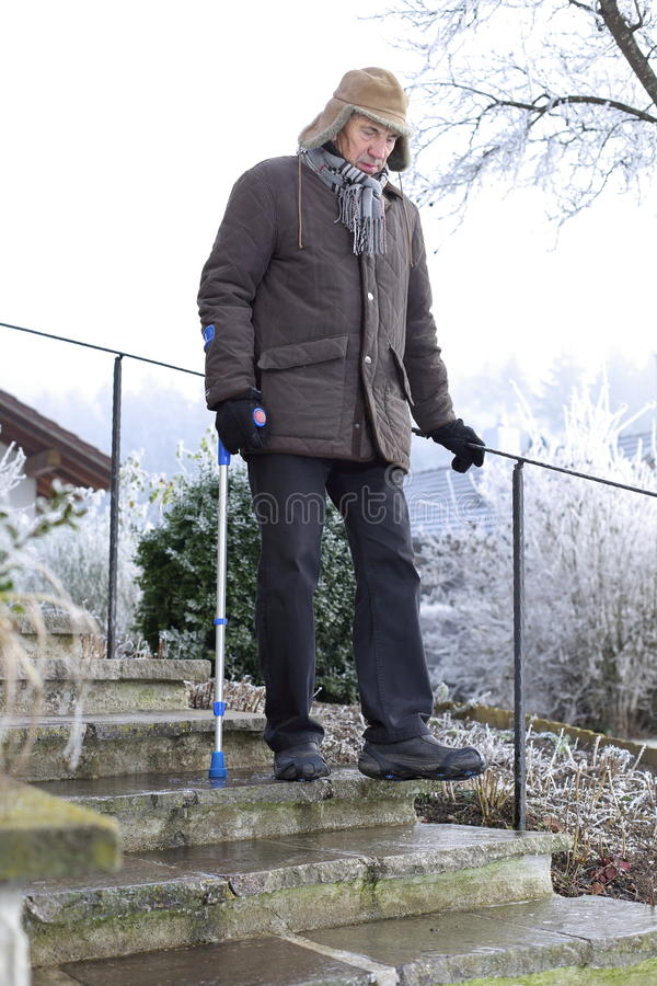 Oude mens op steunpilaren op ijzige treden in de winter stock fotografie