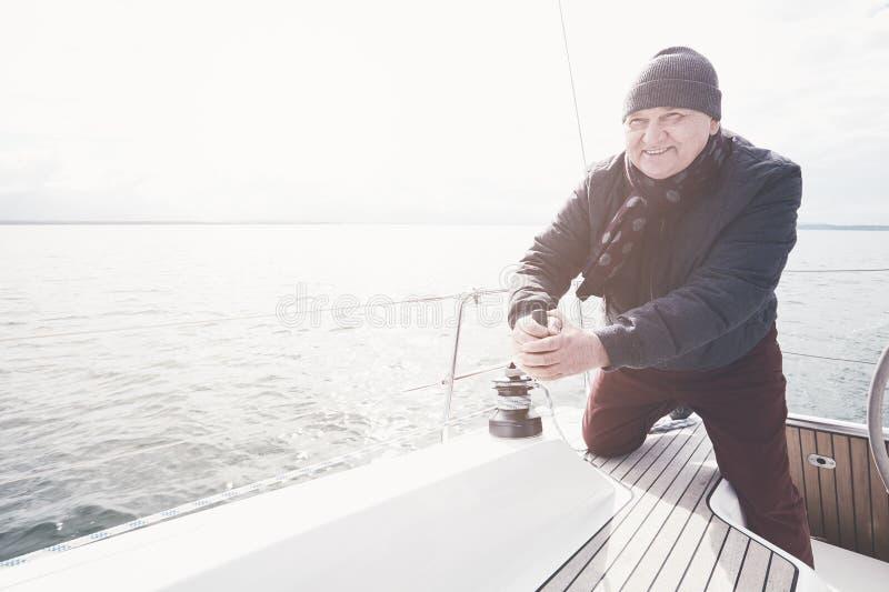Oude mens op zeilboot royalty-vrije stock fotografie