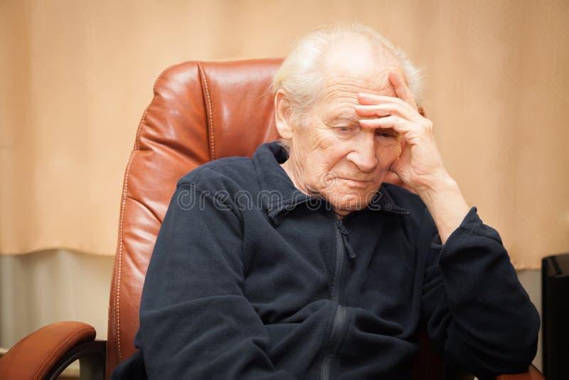 Oude mens pillowes zijn hoofd op een hand stock afbeelding