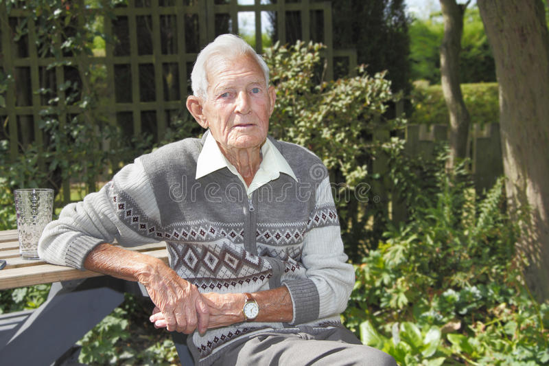 Oude mens in tuin stock afbeeldingen