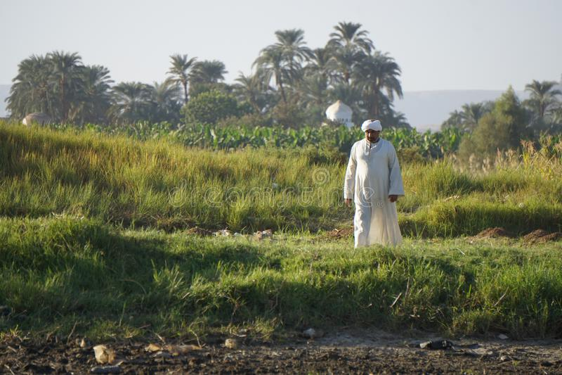 Oude mens in witte robe op de kust van de Nijl royalty-vrije stock afbeeldingen