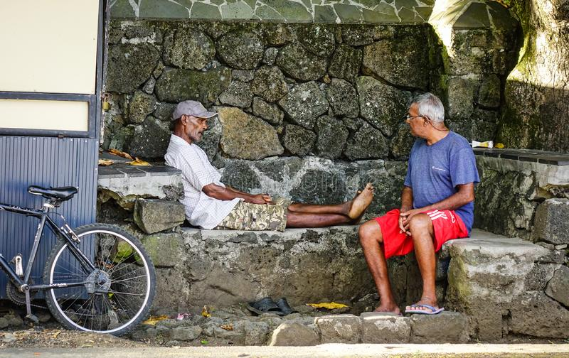 Oude mensen die en in Mauritius zitten babbelen stock fotografie