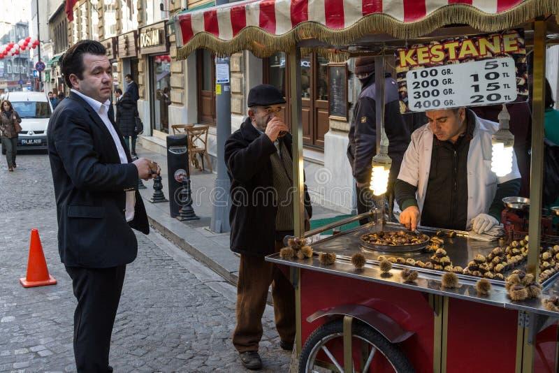 Oude mensen die thee drinken en naast een kiosk roosterende en verkopende kastanjes, een typisch de straatvoedsel van Istanboel v stock foto