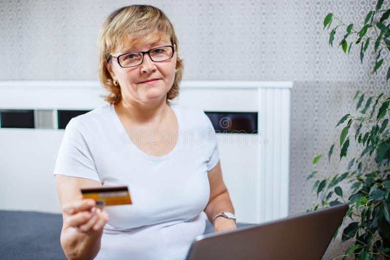 Oude mensen en modern technologieconcept Het portret van jaren '50 rijpt de holdingscreditcard van de vrouwenhand stock afbeelding