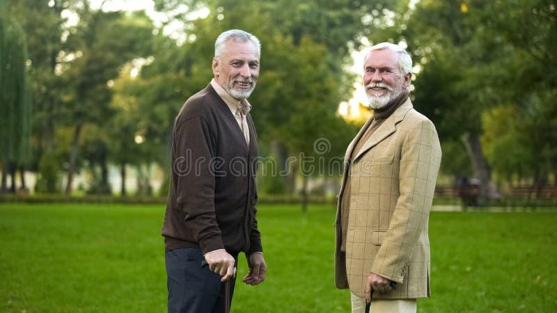 Oude mensen met wandelstokken die en voor camera, mannelijke vriendschap rusten glimlachen stock foto's
