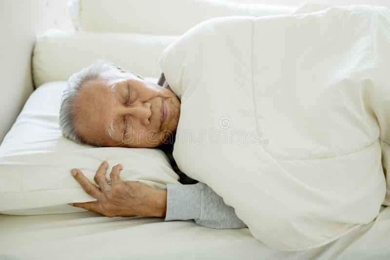 Oude mensenslaap goed op het bed royalty-vrije stock afbeelding