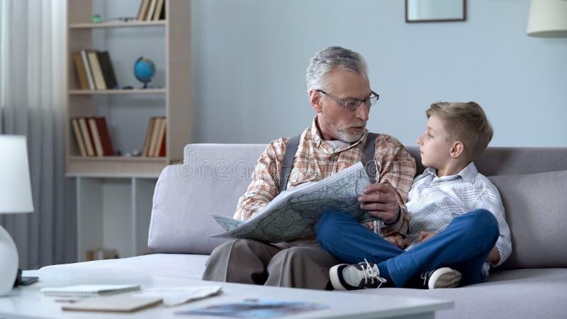 Oude mensenveteraan het bekijken kaart met kleinzoon die frontlijn tonen, die oorlog herinneren royalty-vrije stock fotografie