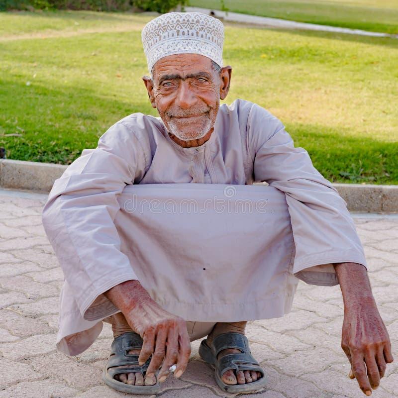 Oude mensenzitting in het hurken positie, Omani squatts inzake zijn lenden, stock fotografie